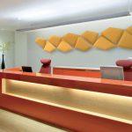 Pannelli fonoassorbenti fissati a parete in composizione decorativa in armonia cromatica con il bancone reception