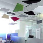 Pannelli fonoassorbenti multicolor orientabili montati su struttura a soffitto fissa in ufficio open space