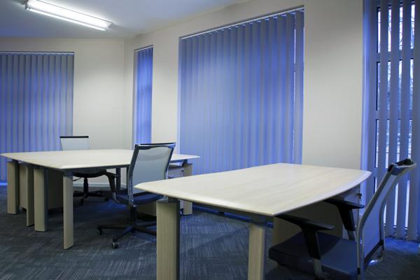 Le tende da ufficio verticali scorrono in senso orizzontale; le lamelle orientabili consentono di modulare il passaggio della luce (fonte: Web)