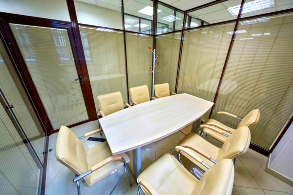 Una tenda da ufficio veneziana per garantire la privacy - quando necessaria - in una sala riunioni realizzata con pareti divisorie in cristallo