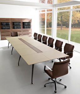 Il tavolo riunioni è rivestito in pelle ed ha al centro un vano per il passaggio dei cavi. La soluzione è di Quinti Sistemi.