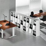 Una libreria free standing bassa divide le aree di lavoro e può ospitare macchine da ufficio (in foto, una soluzione Colombini).