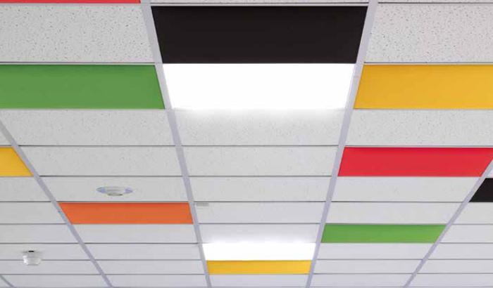 Un controsoffitto allegro e funzionale grazie alle colorate quadrotte fonoassorbenti.