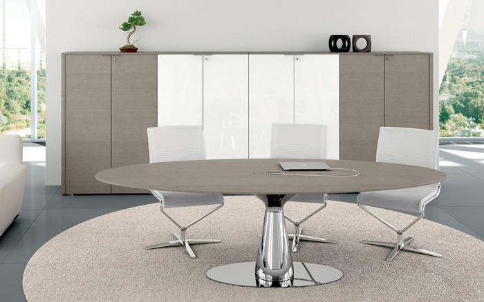 Questo tavolo riunione di forma circolare ha un raffinato piano di lavoro in rovere grigio ed una tondeggiante base cromata lucida. [Bralco]