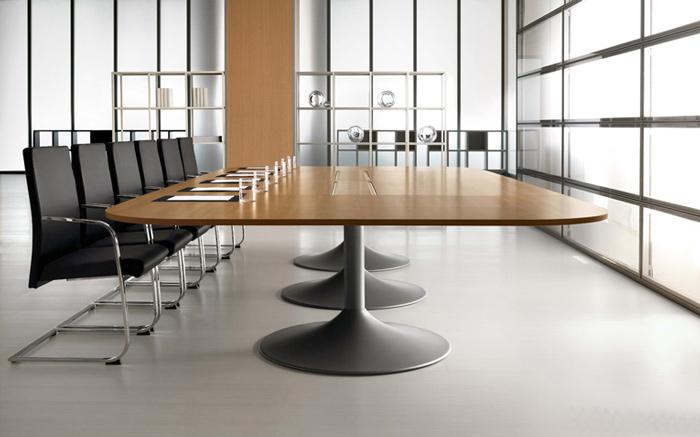 Questo ampio tavolo riunioni ha un design che coniuga perfettamente classico e moderno: il top è laccato noce, mentre la base ha una forma innovativa ed è in acciaio satinato. Sul piano di lavoro sono presenti le fessure per i cavi. [Della Rovere]